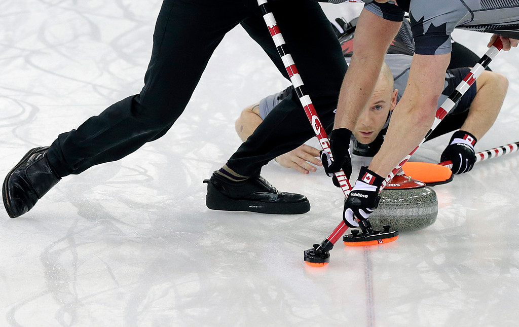. Canada\'s Ryan Fry, center, delivers the rock while teammates Ryan Harnden, left, and E.J. Harnden, right, sweep the ice during the men\'s curling gold medal game against Britain at the 2014 Winter Olympics, Friday, Feb. 21, 2014, in Sochi, Russia. (AP Photo/Wong Maye-E)