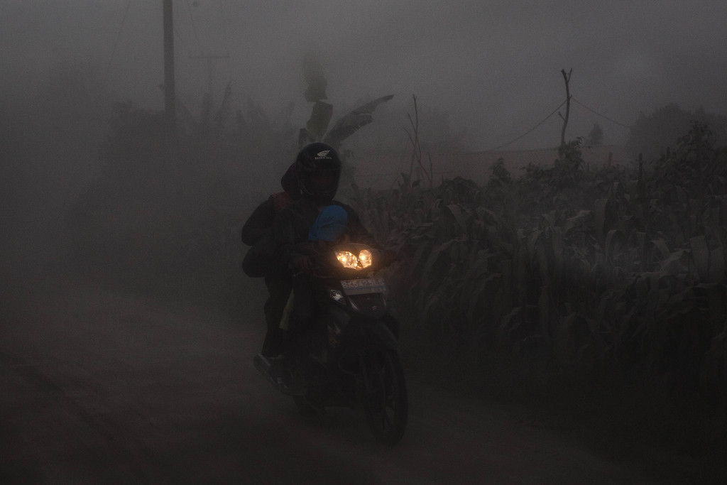 . A motorcyclist passing through an area covered by ash after Mount Sinabung erupted spewing volcanic materials on October 13, 2014 in Berastagi, Karo district, North Sumatra, Indonesia. Mount Sinabung, which had lain dormant for over 400 years, has been intermittently erupting since September 15 last year, killing 15 people and forcing hundreds to flee their homes. According to The National Disaster Mitigation Agency, more than 3,000 residents are still displaced. (Photo by Ulet Ifansasti/Getty Images)