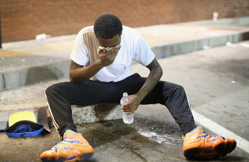 . A man is overcome by tear gas which police launched at demonstrators protesting the killing of teenager Michael Brown on August 17, 2014 in Ferguson, Missouri. Police shot smoke and tear gas into the crowd of several hundred as they advanced near the police command center which has been set up in a shopping mall parking lot. Brown was shot and killed by a Ferguson police officer on August 9. Despite the Brown family\'s continued call for peaceful demonstrations, violent protests have erupted nearly every night in Ferguson since his death.  (Photo by Scott Olson/Getty Images)