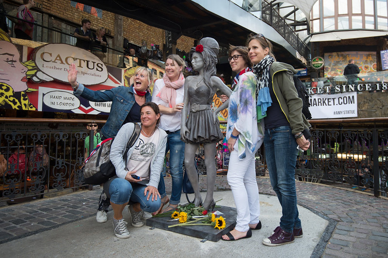. People pose for photographs with a new statue of the late singer Amy Winehouse, after it was unveiled in Camden\'s Stables Market, in London, England, Sunday, Sept. 14, 2014. Three years after her death the unveiling coincides with what would have been her 31st birthday. (AP Photo/Tim Ireland)