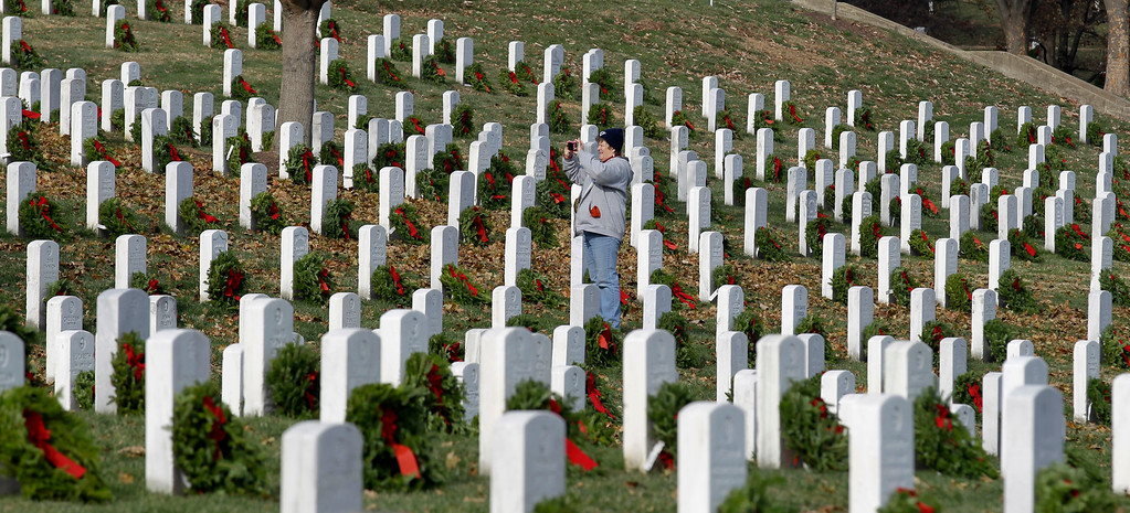 . A unidentified woman takes a picture of tombstones adorned with wreaths during Wreaths Across America\'s 150th anniversary, Saturday, Dec. 13, 2014, at Arlington National Cemetery in Arlington, Va. (AP Photo/Luis M. Alvarez)