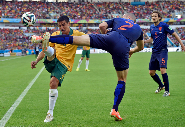 . Australia\'s Tim Cahill, left, and Netherlands\' Ron Vlaar battle for the ball during the group B World Cup soccer match between Australia and the Netherlands at the Estadio Beira-Rio in Porto Alegre, Brazil, Wednesday, June 18, 2014.   (AP Photo/Martin Meissner)