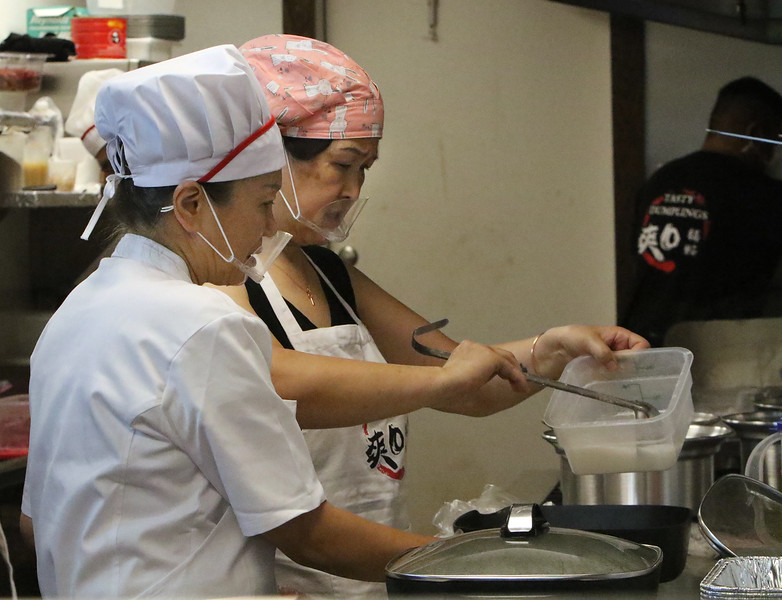 Opening of Tasty Dumplings, new restaurant on Market Street at Cardinal O'Connell Parkway. Cuiping Liu, left, and Jianmei Jin, both aunt of owner Michelle Wang, who have been living in Lowell temporarily to help the restaurant get set up, help out in the kitchen. (SUN/Julia Malakie)
