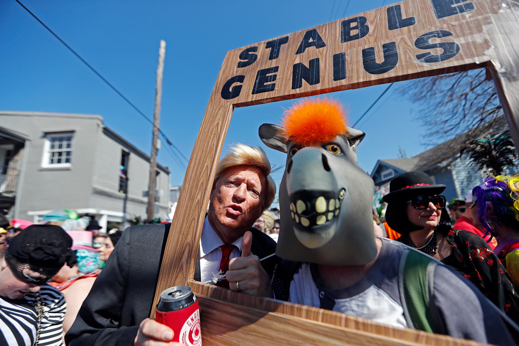 . John Shreves, left, of New Orleans, dressed as Donald Trump, poses with a random reveler with a reference to a well known quote by Trump, during the Society de Sainte Anne parade, on Mardi Gras day in New Orleans, Tuesday, Feb. 13, 2018. (AP Photo/Gerald Herbert)