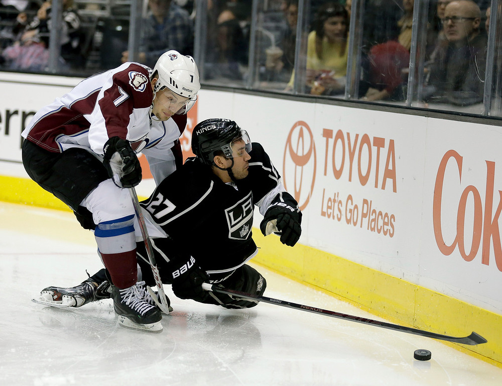 . Colorado Avalanche center John Mitchell, left, knocks Los Angeles Kings defenseman Alec Martinez to the ice during the third period of an NHL hockey game, Saturday, Dec. 21, 2013, in Los Angeles. (AP Photo/Chris Carlson)