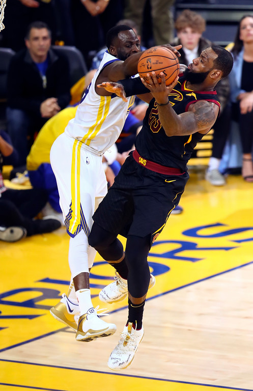 . Cleveland Cavaliers forward LeBron James, right, shoots against Golden State Warriors forward Draymond Green during the second half of Game 1 of basketball\'s NBA Finals in Oakland, Calif., Thursday, May 31, 2018. (AP Photo/Ben Margot)