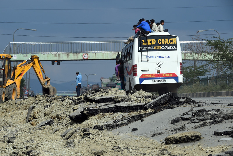 . Nepalese people travel on the roof of a bus as they drive past a damaged road on the outskirts of Kathmandu on April 26, 2015. International aid groups and governments intensified efforts to get rescuers and supplies into earthquake-hit Nepal on April 26, but severed communications and landslides in the Himalayan nation posed formidable challenges to the relief effort.  PRAKASH SINGH/AFP/Getty Images