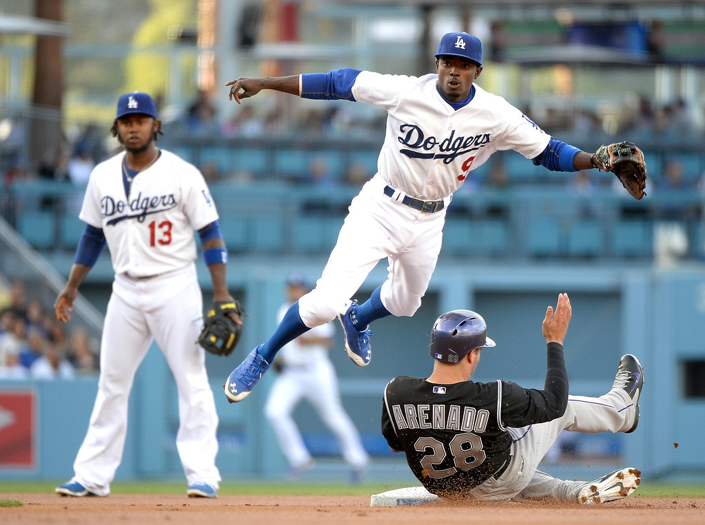 . Dee Gordon #9 of the Los Angeles Dodgers reacts to his throw for a double play over Nolan Arenado #28 of the Colorado Rockies as Hanley Ramirez #13 looks on during the first inning at Dodger Stadium on April 26, 2014 in Los Angeles, California.  (Photo by Harry How/Getty Images)