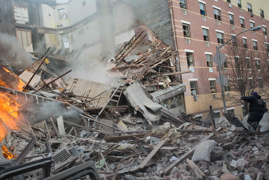 . Emergency workers respond to the scene of an explosion and building collapse in the East Harlem neighborhood of New York, Wednesday, March 12, 2014.  (AP Photo/Jeremy Sailing)