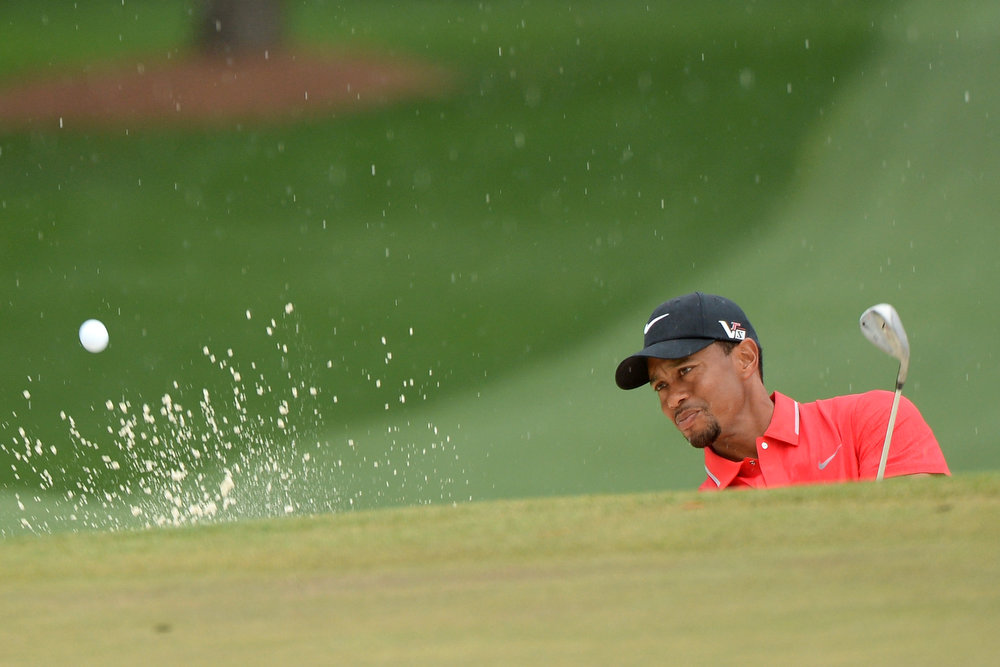 Description of . Tiger Woods of the United States hits out of a bunker on the 7th hole during the final round of the 2013 Masters Tournament at Augusta National Golf Club on April 14, 2013 in Augusta, Georgia.  (Photo by Harry How/Getty Images)