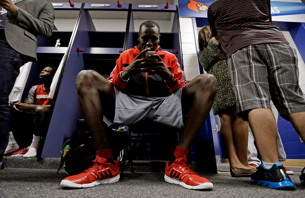 . Louisville\'s Gorgui Dieng looks at his phone in the locker room before practice for their NCAA Final Four tournament college basketball game Sunday, April 7, 2013, in Atlanta. Louisville plays Michigan in the championship game on Monday. (AP Photo/Charlie Neibergall)