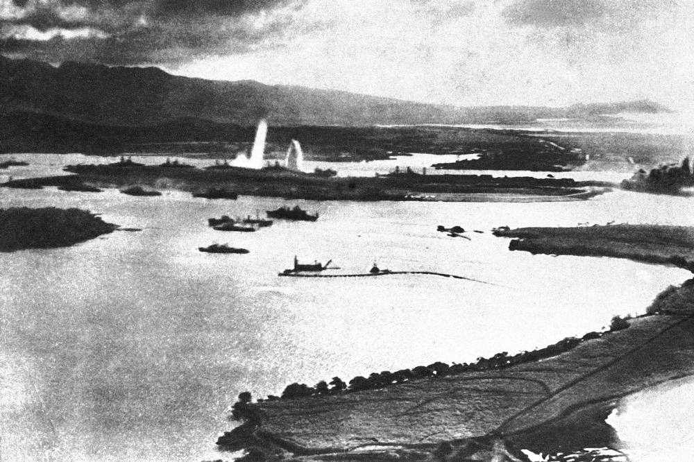 . Panoramic view of Pearl Harbor during the Japanese attack of Dec. 7, 1941.  Note warship in background being hit by torpedo and spouting water.  (AP Photo)