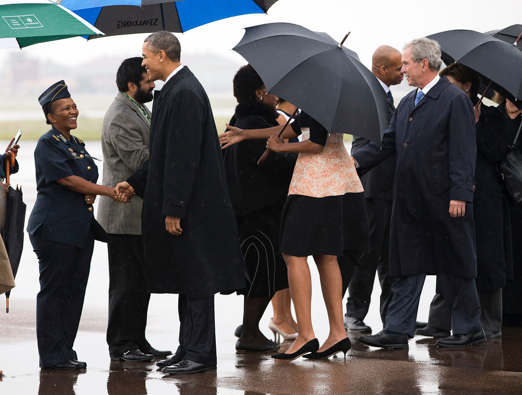 . U.S. President Barack Obama, left, first lady Michelle Obama, under umbrella, and former President George W. Bush are greeted as they arrive at Waterkloof Air Base for a memorial service in honor of former South African leader Nelson Mandela on Tuesday, Dec. 10, 2013, in Centurion, South Africa. World leaders, celebrities, and citizens from all walks of life gathered for a memorial service on Tuesday to pay respects to Mandela. (AP Photo/ Evan Vucci)