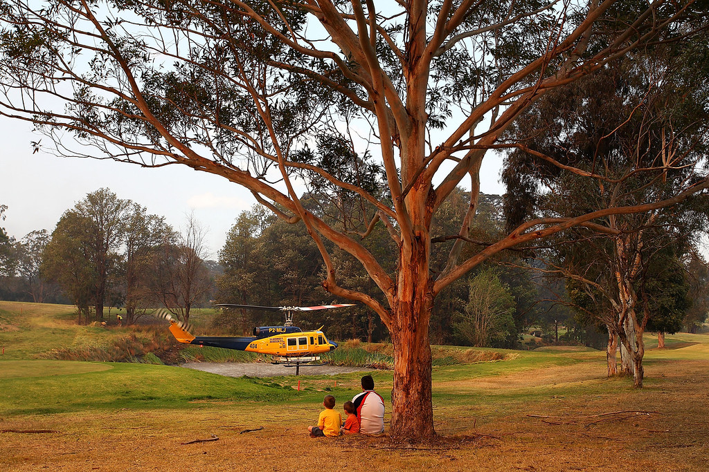. A helicopter collects water from a golf course dam at the Winmalee Country Club on October 18, 2013 in Winmalee, Australia.  (Photo by Lisa Maree Williams/Getty Images)