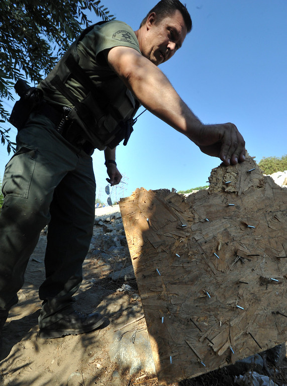 . A Los Angeles County Sheriff\'s Deputy finds a board with nails set as a booby trap as they search a homeless camp in the river bed area of the San Gabriel River near South El Monte on Thursday September 12, 2013. (Whittier Daily News/Staff Photo by Keith Durflinger)
