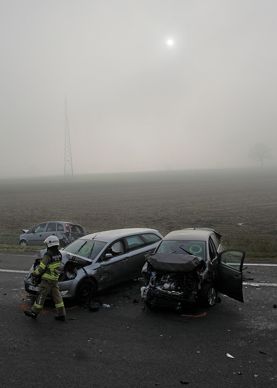 . A firefighter passes crashed cars on the A19 highway in Zonnebeke, western Belgium, Tuesday, Dec.3, 2013.   (AP Photo/Yves Logghe)