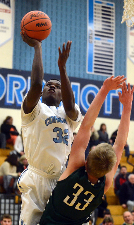 . Waterford Mott\'s #32 Dmonta Harris goes up for a shot over West Bloomfield\'s #33 Zach Allread during their game at Waterford Mott High School, Thursday December 12, 2013. West Bloomfield went on to win the game 55-52. (Vaughn Gurganian-The Oakland Press)