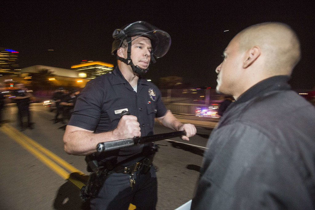 . A police officer confronts a demonstrator on November 26, 2014 in Los Angeles during demonstrations against a decision by a Ferguson, Missouri grand jury to not indict a white police officer in the shooting of black teenager Michael Brown.  Violent protests and looting erupted in the US town of Ferguson for a second day after the grand jury\'s decision. AFP PHOTO / Ringo  CHIU/AFP/Getty Images