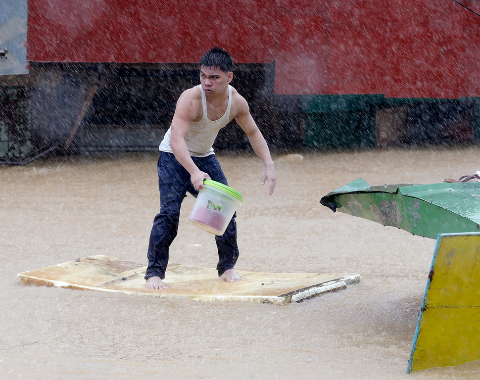 . A resident balances himself on a makeshift floater as he evacuates to safety after heavy monsoon rains spawned by tropical storm Fung-Wong flooded Marikina city, east of Manila, Philippines and most parts of  the metropolis Friday, Sept.19, 2014. (AP Photo/Bullit Marquez)