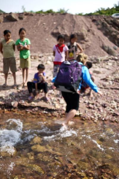 The village children look on with interest as we cross the small river.
