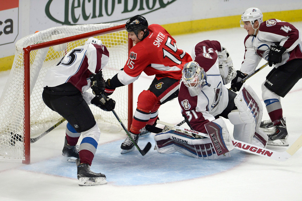. Ottawa Senators\' Zack Smith (15) scores past Colorado Avalanche goaltender Calvin Picard (31) as Avalanche\'s Dennis Everberg (45) and Tyson Barrie (4) defend during the first period of an NHL hockey game Thursday, Ocyt. 16, 2014, in Ottawa, Ontario. (AP Photo/The Canadian Press, Justin Tang)