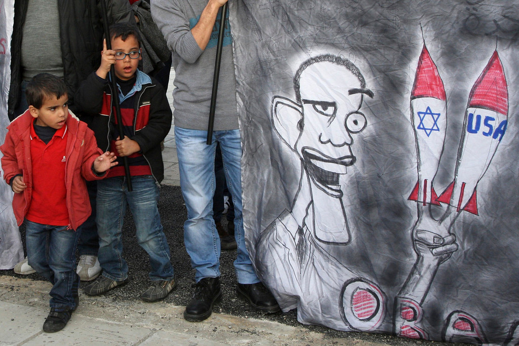 . Children look at a satire of U.S. President Barack Obama during a demonstration against his visit in front of the U.S. embassy in Amman, March 21, 2013. Obama will arrive in Jordan on Friday as part of his visit to the region. REUTERS/Majed Jaber