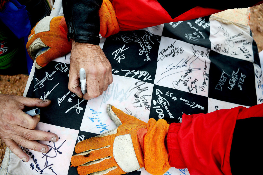. Sidecar racer Bruno Marlin signs the finish line flag after completing the 91st running of the Pikes Peak International Hill Climb Sunday, June 30, 2013. All competitors were encouraged to sign the flags that will soon have a place in the Pikes Peak Hill Climb Museum. (Michael Ciaglo, The Gazette)