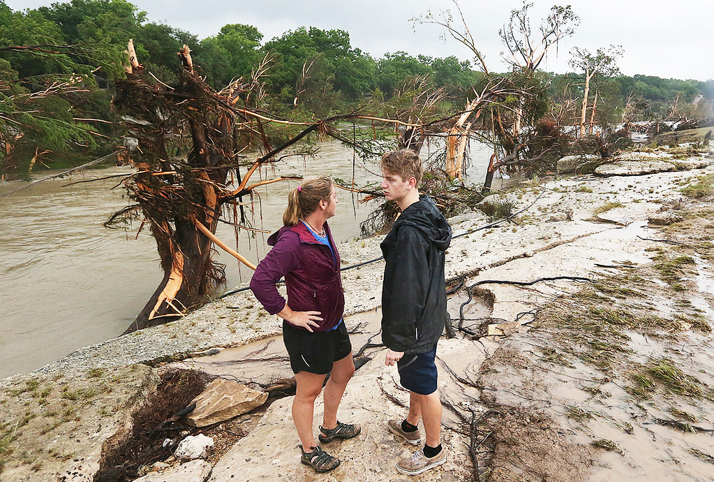 . Shelly Guzal and her son Grant stand by the Blanco River where a house once stood, Monday, May 25, 2015, in Wimberley, Texas. Corpus Christi resident Jonathan McComb and his family were guests in the house when it was swept away by floodwaters. McComb escaped but his family is missing. Several people were reported missing in flash flooding from a line of storms that stretched from the Gulf of Mexico to the Great Lakes. (Jerry Lara/The San Antonio Express-News via AP)