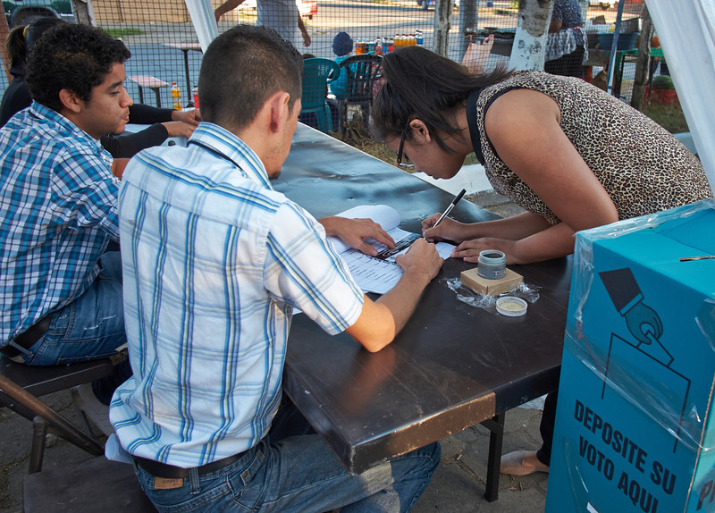 Election day in Santa Ana: <br /> A voter signs the register to affirm that she has cast her vote.