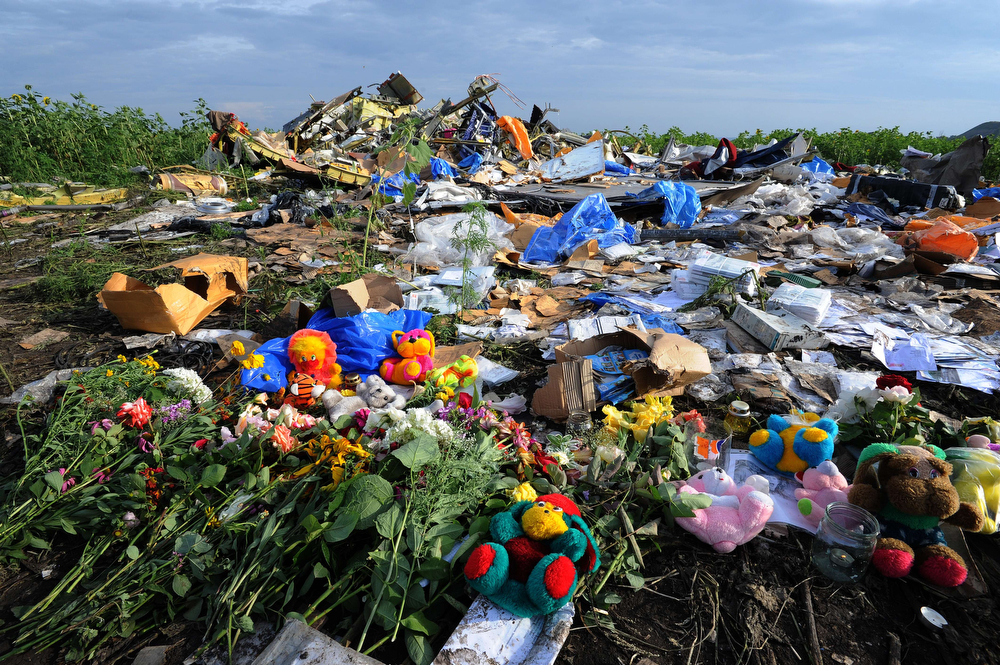 . Flowers and plush toys are left at the site of the crash of a Malaysia Airlines plane carrying 298 people from Amsterdam to Kuala Lumpur in Grabove, in rebel-held eastern Ukraine, on July 19, 2014. Ukraine and pro-Russian insurgents agreed on July 19 to set up a security zone around the crash site of a Malaysian jet whose downing in the rebel-held east has drawn global condemnation of the Kremlin. Outraged world leaders have demanded Russia\'s immediate cooperation in a prompt and independent probe into the shooting down on July 17 of flight MH17 with 298 people on board. (DOMINIQUE FAGET/AFP/Getty Images)