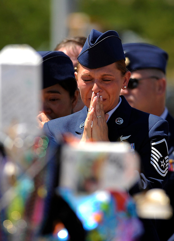 . Raea Thompson, front, and officers from Buckley Air Force Base visit the memorial for victims of the Aurora Theater Shooting in Aurora, CO on Saturday, July 28, 2012. Hyoung Chang, The Denver Post