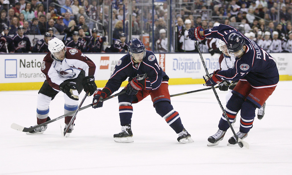 . Columbus Blue Jackets\' Nick Foligno (71) feeds the puck to teammate Blake Comeau (14) who is defended by Colorado Avalanche\'s Nate Guenin (5) during the second period of an NHL hockey game, Tuesday, April 1, 2014, in Columbus, Ohio. Comeau scored to make it 2-0. (AP Photo/Mike Munden)