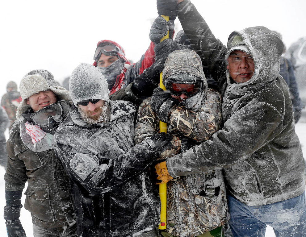 . Military veterans huddle together to hold a United States flag against strong winds during a march to a closed bridge outside the Oceti Sakowin camp where people have gathered to protest the Dakota Access oil pipeline in Cannon Ball, N.D., Monday, Dec. 5, 2016. (AP Photo/David Goldman)