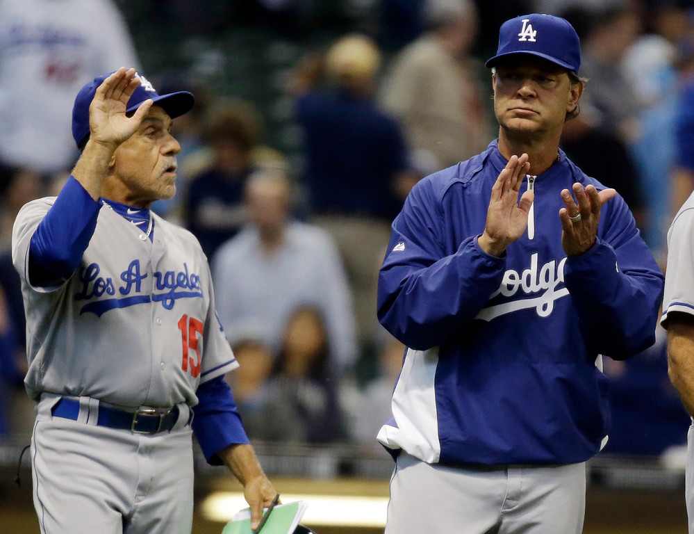 . Los Angeles Dodgers manager Don Mattingly celebrates with Davey Lopes (15) after a baseball game against the Milwaukee Brewers Wednesday, May 22, 2013, in Milwaukee. The Dodgers won 9-2. (AP Photo/Morry Gash)