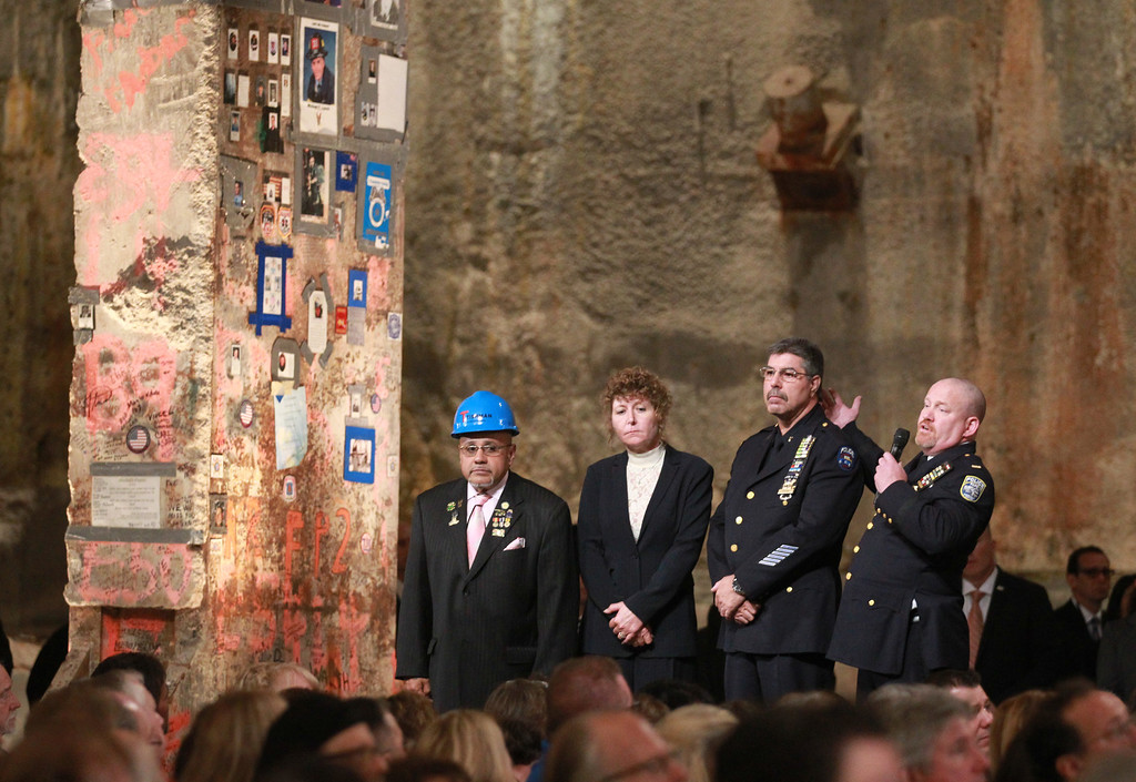 """. First responders Manny Rodriguez, Pia Hofmann, Det. Anthony Favara, of the NYPD and Lt. Stephen Butler, of the Port Authority Police, speak next to the \""""Last Beam\"""" during the dedication ceremony at the National September 11 Memorial May 15, 2014 in New York City.  (Photo by John Munson-Pool/Getty Images)"""