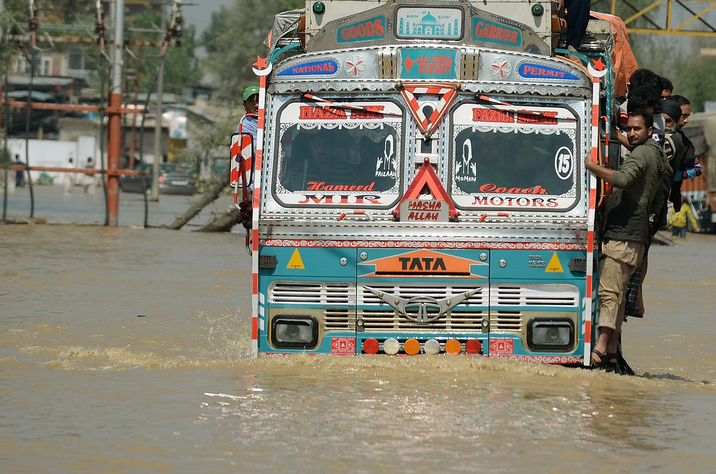 . Kashmiri men travel on a truck through the floodwaters in Srinagar on September 10, 2014.   AFP PHOTO/ PUNIT  PARANJPE/AFP/Getty Images