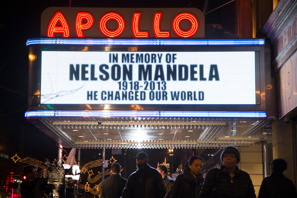 . Pedestrians pass beneath the Apollo Theatre marquee commemorating the life of South African leader Nelson Mandela, Thursday, Dec. 5, 2013, in the Harlem neighborhood of New York. South Africa\'s first black president died Thursday after a long illness. He was 95. (AP Photo/John Minchillo)