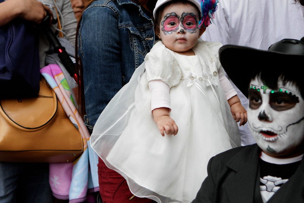 . Six-month-old Melody, dressed as a calavera, is carried by her mother through the crowd that is gathering for the start of the Gran Procession of the Catrinas, to mark the upcoming Day of the Dead holiday, in Mexico City, Sunday, Oct. 23 2016. The gran procession is one of many that will take place in Mexico City as part of the celebrations, culminating with visits to the graves of departed loved ones on Nov. 1 and 2. The figure of a skeleton wearing broad-brimmed hat was first done as a satirical engraving by artist Jose Guadalupe Posada sometime between 1910 and his death in 1913, to poke fun at women who pretended to be European by dressing elegantly and as a critique of social stratification. (AP Photo/Anita Baca)