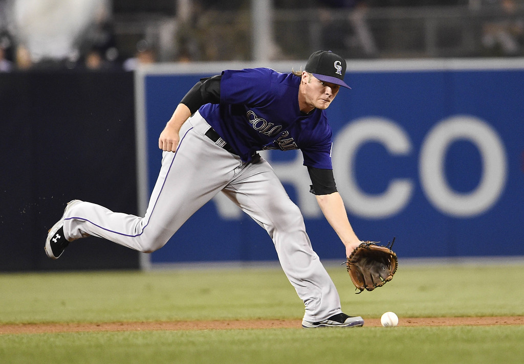 . SAN DIEGO, CA - SEPTEMBER 22:  Josh Rutledge #14 of the Colorado Rockies makes the stop on a ball off the bat of Yangervis Solarte #27 of the San Diego Padres during the first inning of a baseball game at Petco Park September, 22, 2014 in San Diego, California. Rutledge got the out at first base.  (Photo by Denis Poroy/Getty Images)