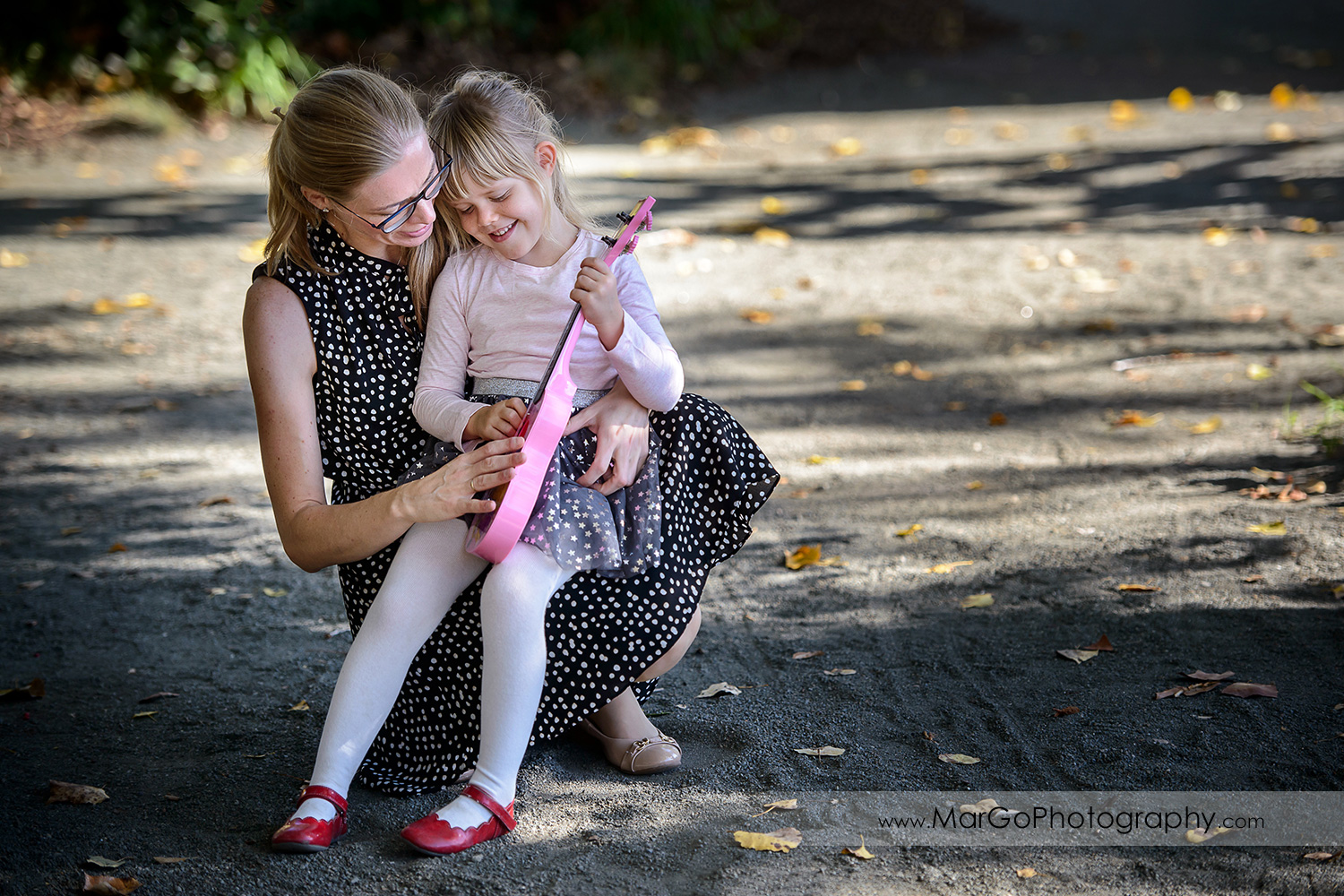 little girl sitting on her mom's laps and playing pink guitar at Mountain View Shoreline Lake Park