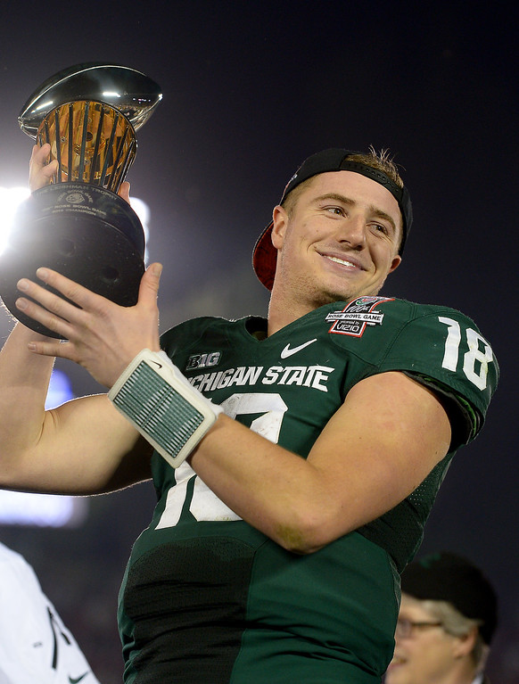 . Michigan State quarterback Connor Cook holds up the trophy after beating Stanford 24-20 at the Rose Bowl, Wednesday, January 1, 2014. (Photo by Michael Owen Baker/L.A. Daily News)
