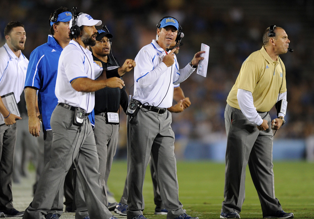 . UCLA head coach Jim Mora, second from right, and his staff give instruction to their players against Nevada, Saturday, August 31, 2013, at the Rose Bowl. (Michael Owen Baker/L.A. Daily News)
