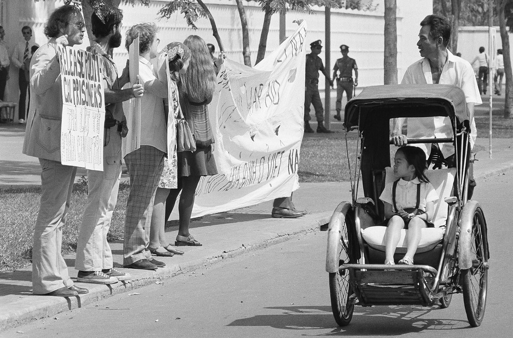 . A little girl in a pedicab, and her driver stare as they pass a demonstration of nine anti-war activists before the United States embassy in Saigon, Friday, Jan. 25, 1975. The activists, led by David Harris, left, of Menlo Park, Calif. former husband of folk singer Joan Baez, passed out leaflets demanding the end of U.S. intervention in South Vietnam. (AP Photo)