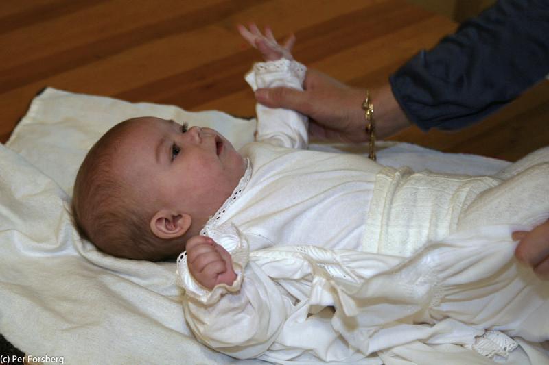 Det var ingen lätt uppgift att få på dopklänningen, eftersom Meja ville rulla runt hela tiden...