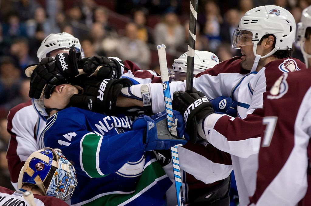 . Vancouver Canucks\' Alex Burrows, left, is roughed up by Colorado Avalanche\'s Jan Hejda, back left, of the Czech Republic, and Ryan O\'Byrne, right, during the first period of an NHL hockey game in Vancouver, British Columbia, on Wednesday, Jan. 30, 2013. (AP Photo/The Canadian Press, Darryl Dyck)
