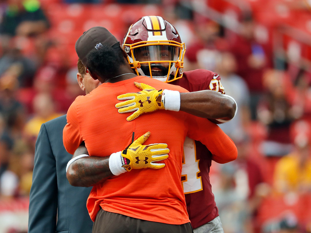 . Cleveland Browns injured quarterback Robert Griffin III hugs Washington Redskins tight end Niles Paul (84) before an NFL football game Sunday, Oct. 2, 2016, in Landover, Md. (AP Photo/Carolyn Kaster)