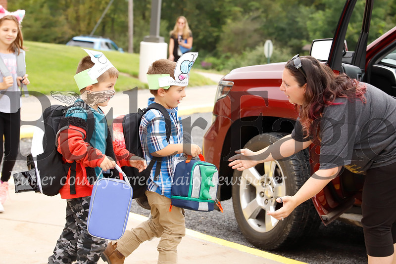 Ethan, 6,(left) and Evan Brewer get ready to hug their mom, Sara Brewer after school Tuesday at Dassa McKinney Elementary in the  Moniteau school district. Seb Foltz/Butler Eagle