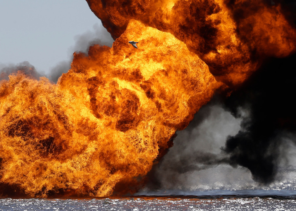 . A seagull, top center, is seen flying in front of a fire that still burns after a tugboat and barge hit a gas pipeline yesterday evening in Perot Bay in Lafourche Parish, La., Wednesday, March 13, 2013. (AP Photo/Gerald Herbert)