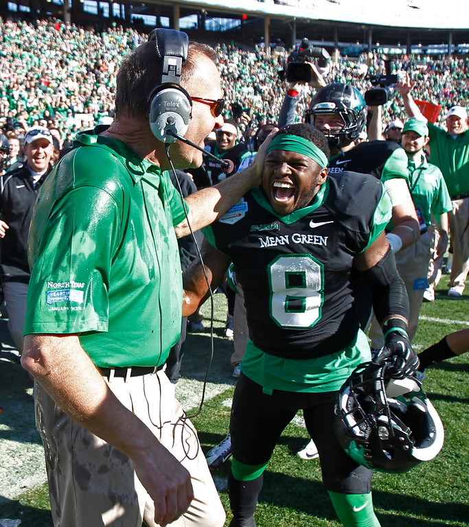 . North Texas head coach Dan McCarney, left, celebrates with defensive back Marcus Trice (8) following their 36-14 win over UNLV in the Heart of Dallas NCAA college football game, Wednesday, Jan. 1, 2014, in Dallas. (AP Photo/Mike Stone)
