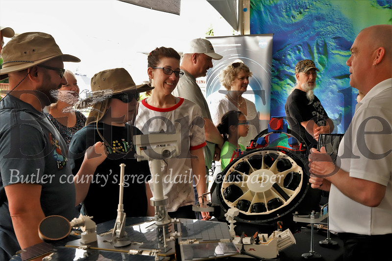 Jeffrey (left), Enzo and Nancy Lee Federoff learn about the Mars Rover program from NASA program scientist Mitch Schulte at this year's Mars celebration. Seb Foltz/Butler Eagle